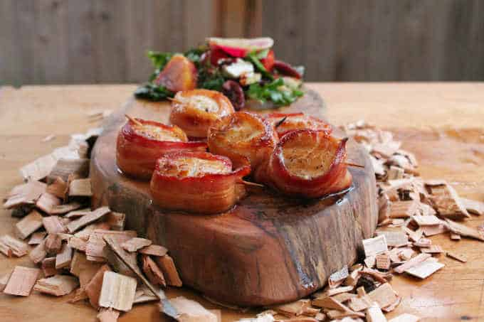 Scallops wrapped in bacon and grilled with maple syrup on wood slab and wood chips with green salad