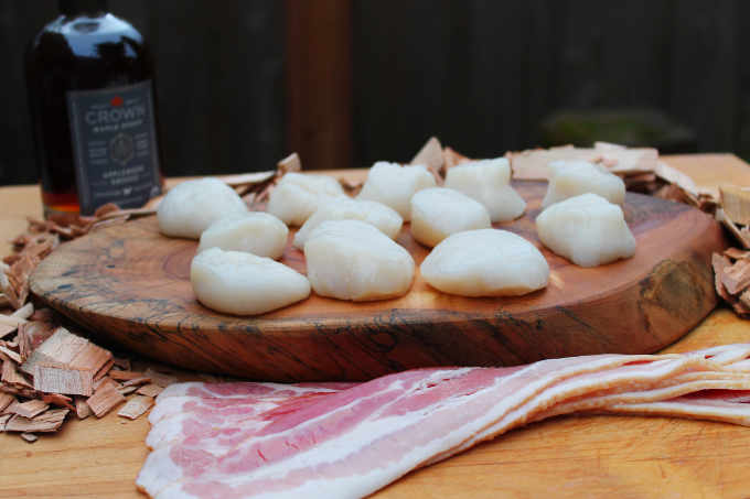 raw scallops sitting on wood slab and cherry wood chips with alder wood smoked maple syrup and bacon slices