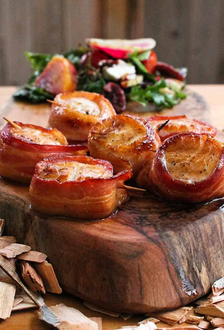 scallops wrapped in bacon and brushed with alder wood smoked maple syrup sitting on a wood cutting board