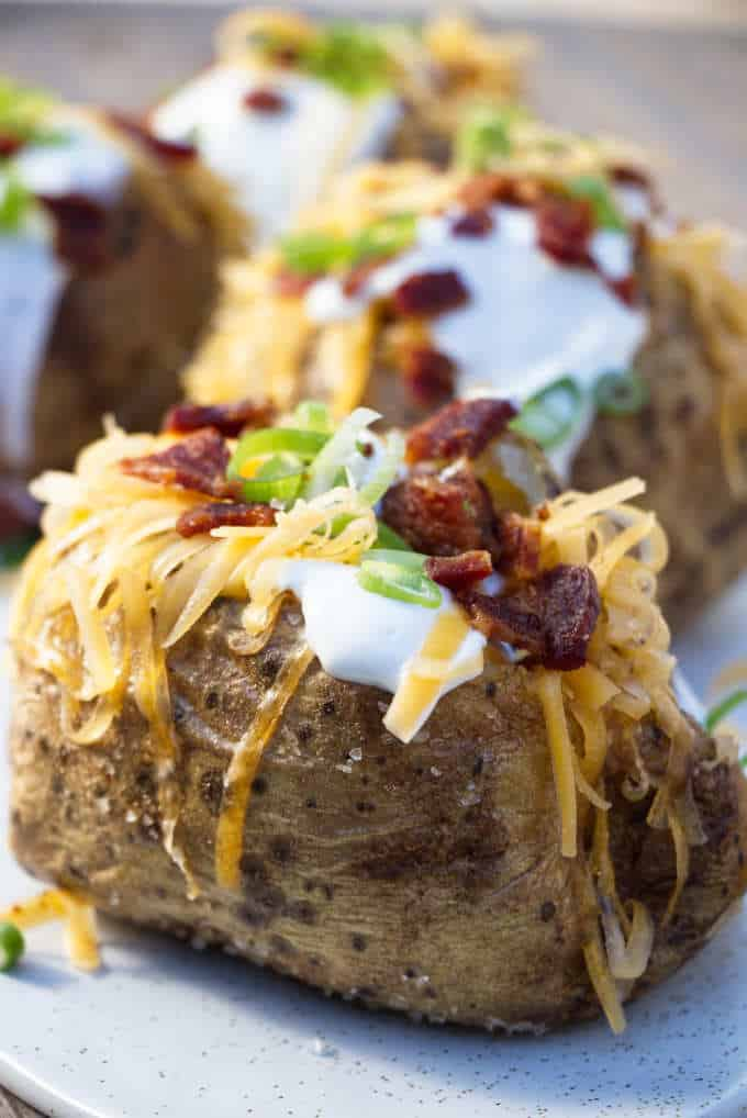 4 air fryer baked potatoes topped with sour cream, cheese, bacon and onions