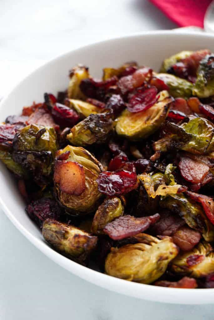 a serving bowl with air fryer Brussels sprouts with bacon onions and cranberries