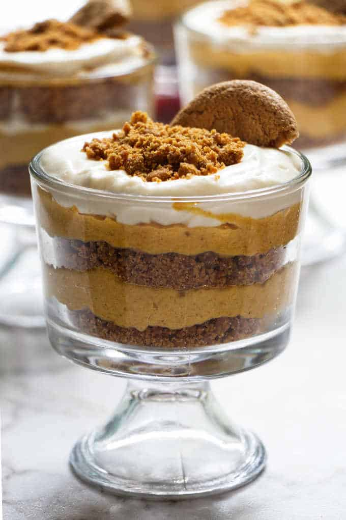 A dish of no bake cheesecake parfait with a gingersnap cookie on top