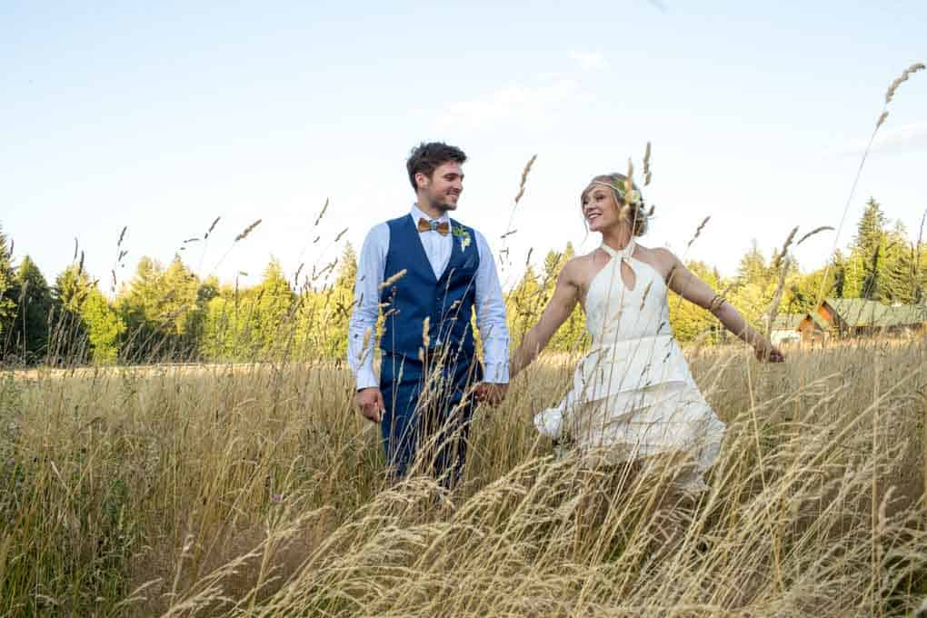 wife and husband on wedding day, man wearing blue vest and blue dress shirt with wooden bow tie and woman wearing white wedding dress with neck straps and flower hair piece standing in a field of wheat