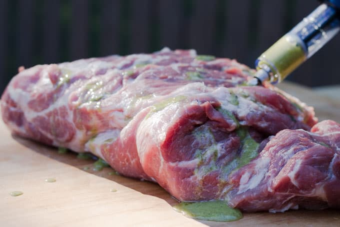 raw piece of pork butt being injected with green marinade sitting on maple wood butcher block