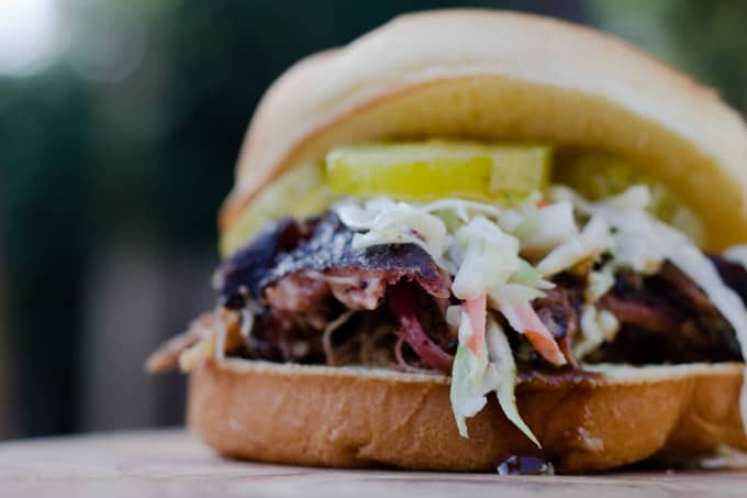 pulled pork sandwich with coleslaw and pickles spilling out of the bun and sitting on a slab of wood