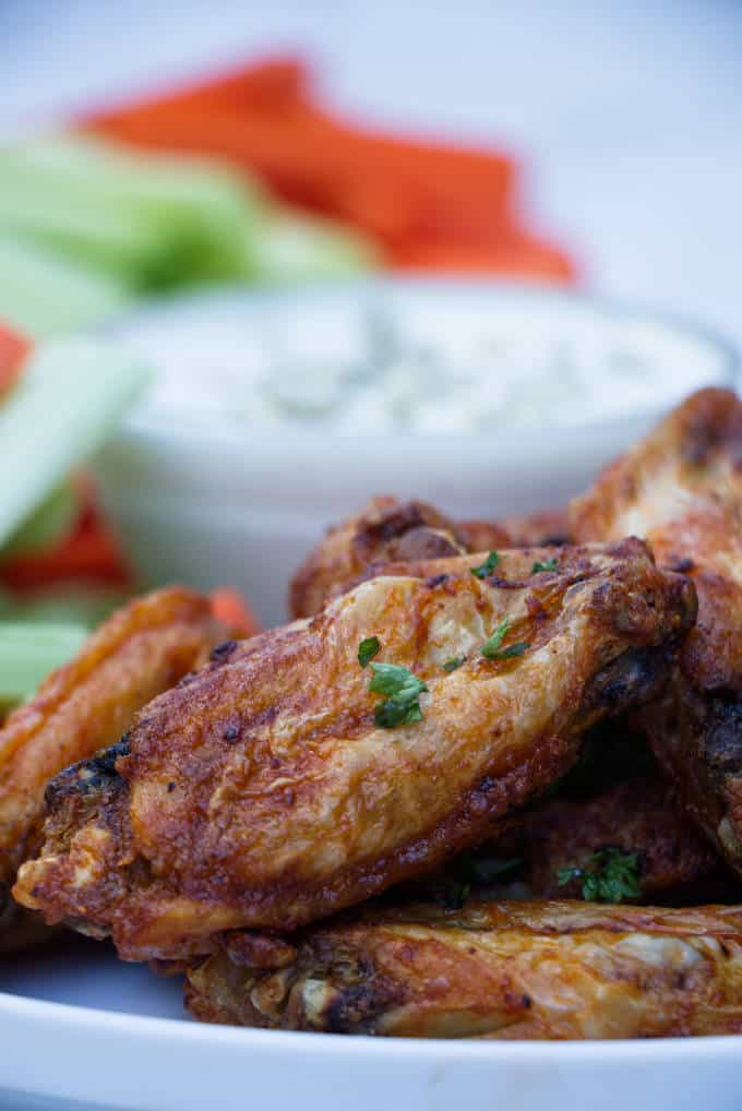 chicken wings with buffalo sauce sitting on a white plate with blue cheese and celery and carrots in the background