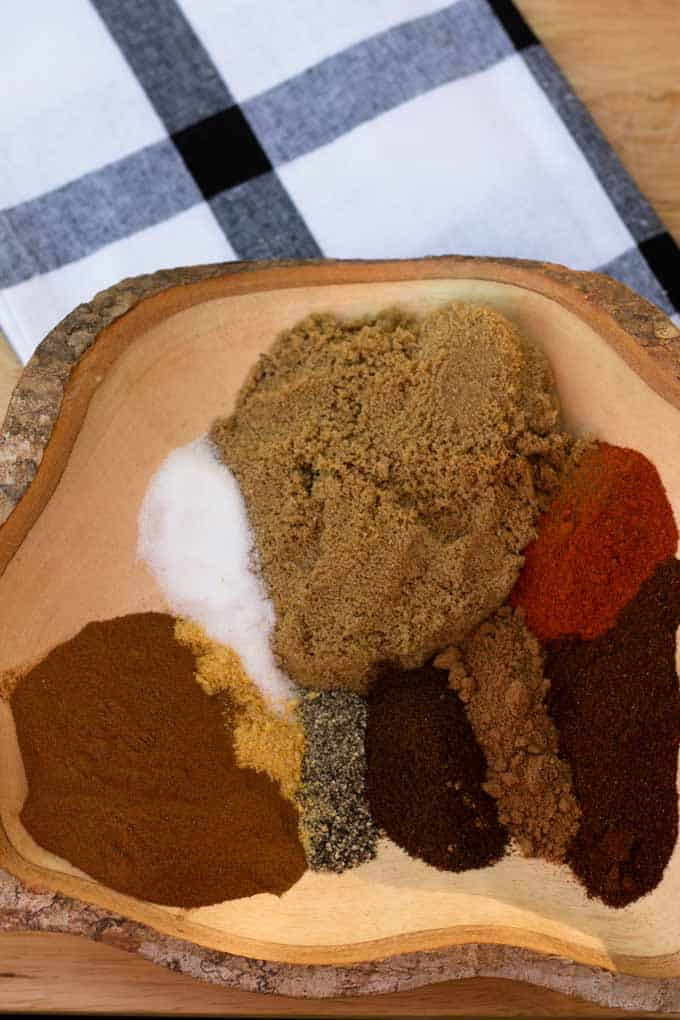 many spices laid next to each other in wooden bowl laying on plaid towel