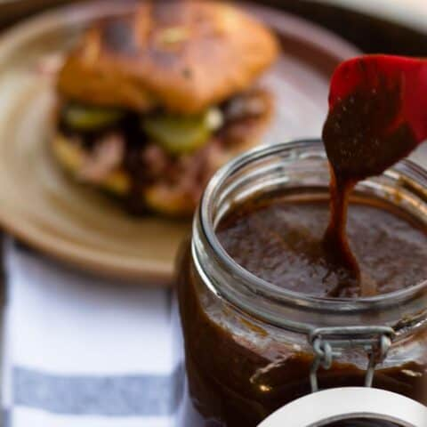 pumpkin spice bbq sauce dripping from utensil and pulled pork sandwich in background