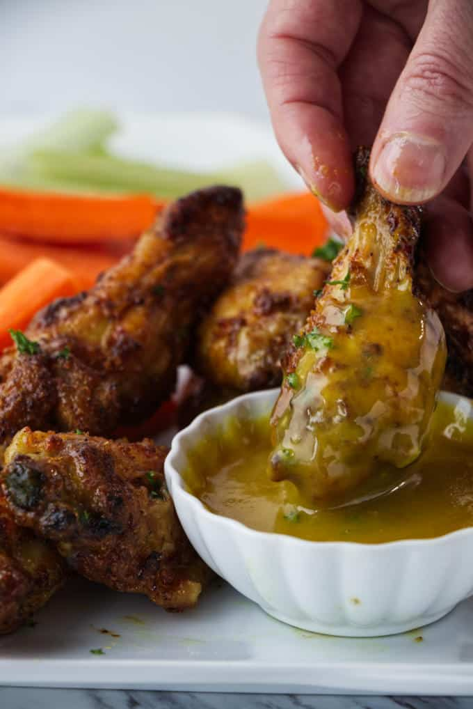 crispy air fried chicken wings sitting on a white plate with sliced carrots and celery with parsley sprinkled on top and one wing being dipped in a dish of honey mustard sauce