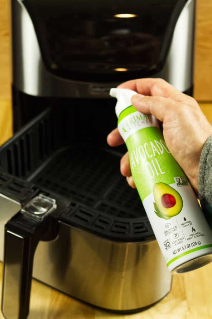 Avocado oil aerosol spray in front of a stainless and black air fryer on a wood table