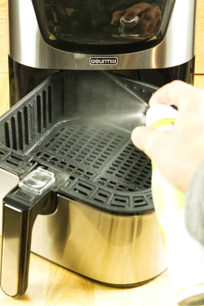 spraying aerosol avocado oil into stainless and black air fryer on wooden table