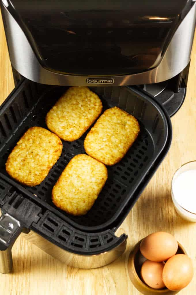 hash browns spaced out in black and stainless air fryer basket with eggs and glass of milk on wood table