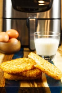 four air fried hash brown patties on wood and blue epoxy cutting board with glass of milk and bowl of brown eggs in back ground and stainless air fryer
