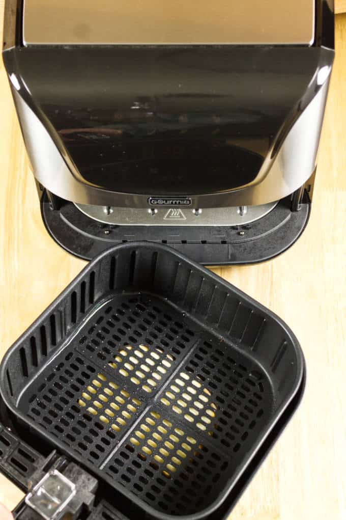 black and stainless air fryer with slice of bread underneath the removable basket and pan on top of wood table