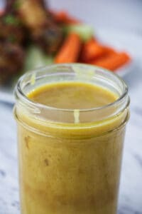 brownish yellow honey mustard sauce in mason jar with chicken wings and carrots and celery on a white plate in the background