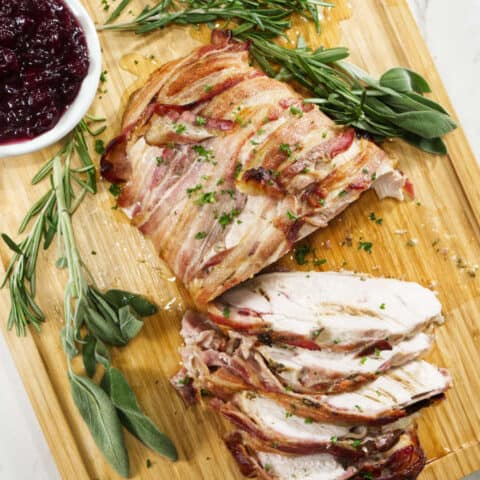 turkey breast wrapped in bacon and sliced sitting on a wooden cutting board with sage in the background with a bowl of cranberry sauce and marble in background