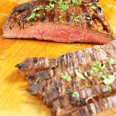 grilled flank steak on wood cutting board sliced into strips medium rare, veggies in background