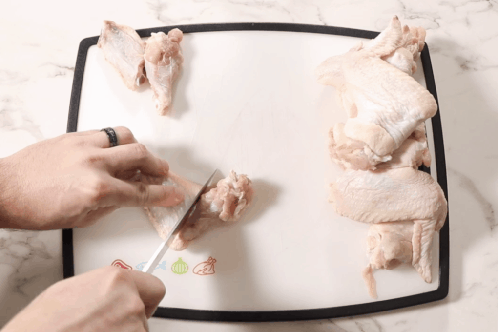 chicken wings on the cutting board and cutting with knife between wingette and drumette