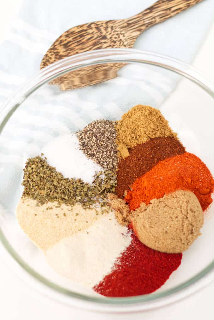 spices for barbecue spice blend arranged in a glass bowl sitting on a white table with blue and white towel