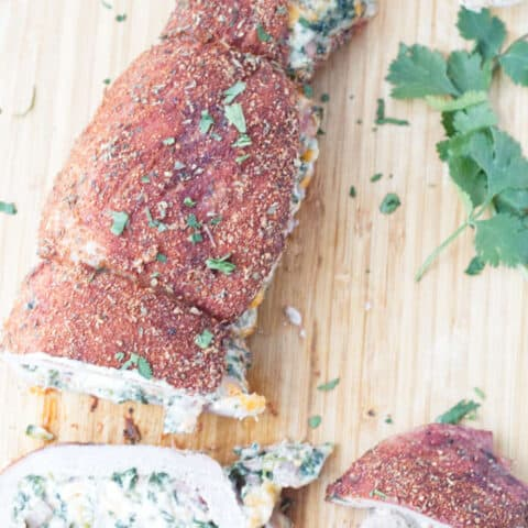 sliced stuffed pork tenderloin with cajun rub and twine holding it together, cheese stuffing, cilantro and garlic cloves sitting on wood