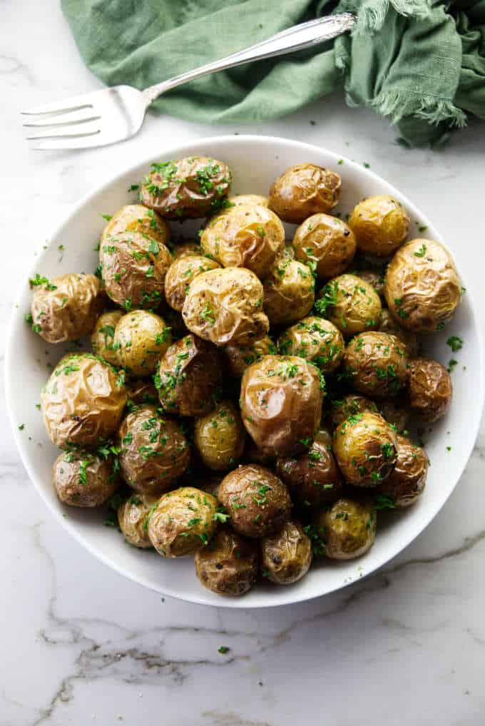 A serving dish of baby parsley potatoes.