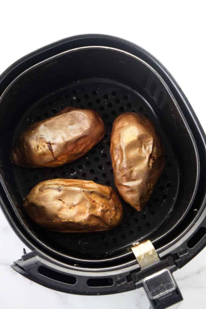 Three sweet potatoes in an air fryer.
