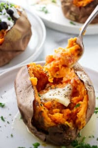 A fork digging into an air fryer baked sweet potato.