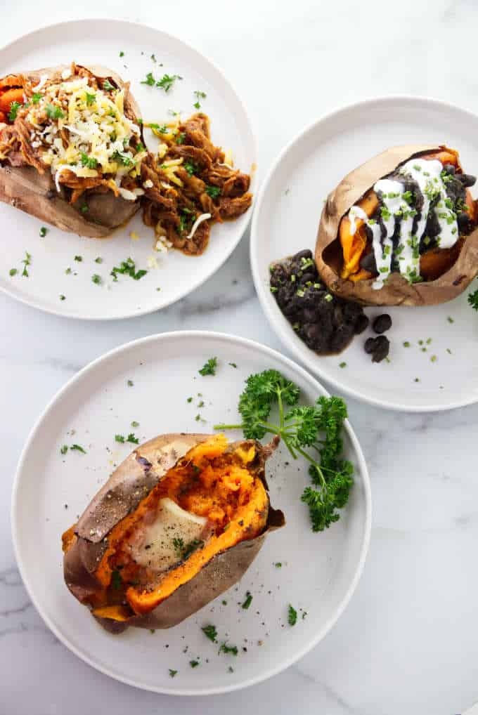 Three air fryer baked sweet potatoes with pulled pork, black beans, and butter.