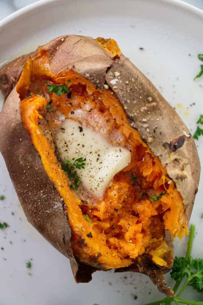 Air fryer baked sweet potato with butter, salt and pepper.