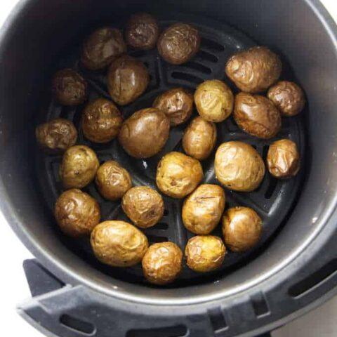 Baby potatoes in an air fryer basket.