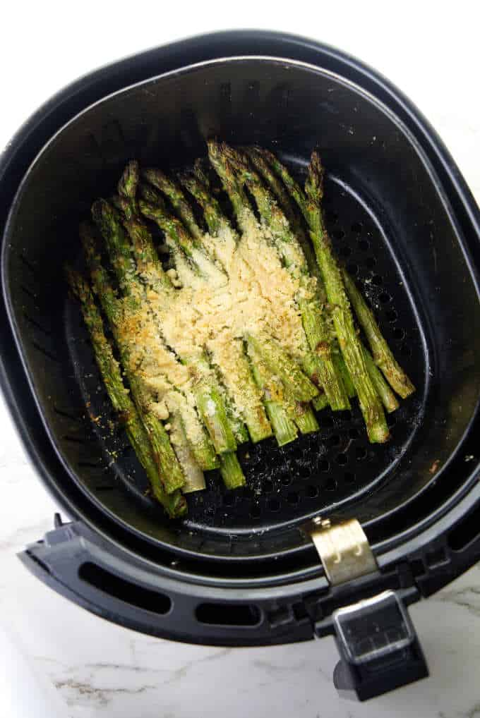 Asparagus in an air fryer basket.