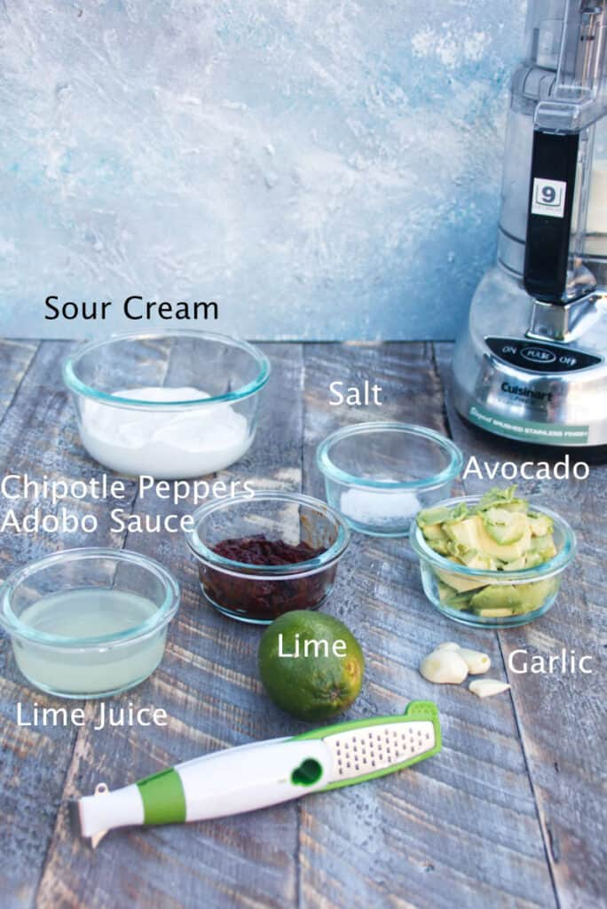 ingredients for chipotle lime crema sour cream, salt, avocado, chipotle peppers, adobo sauce, whole lime for zest, garlic cloves, with food processor and microplane