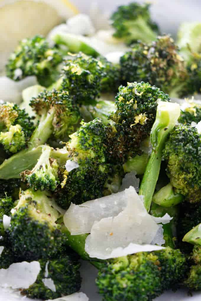 Close up of broccoli with parmesan and lemon.
