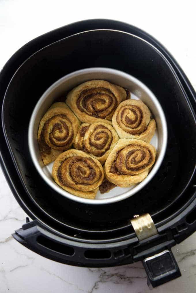 Hot cinnamon rolls in an air fryer basket.