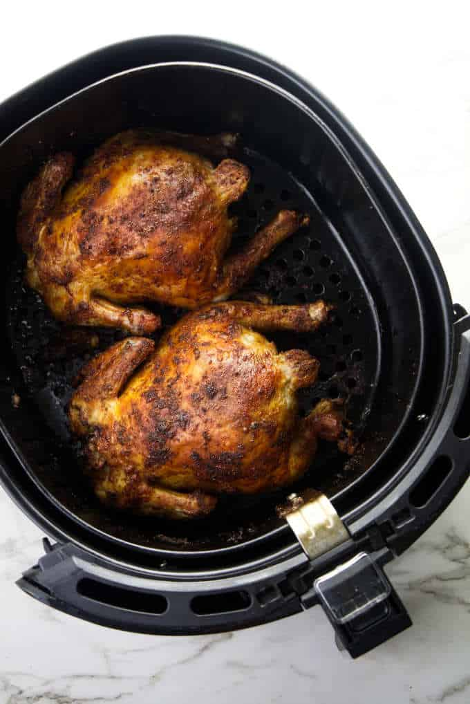 Two Cornish game hens in an Air Fryer basket.