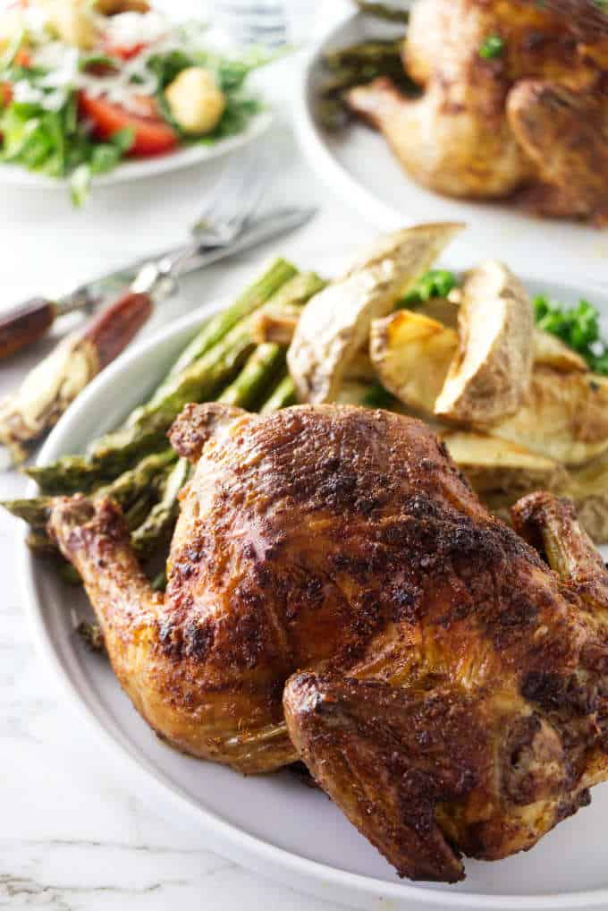 Cornish game hens on a plate with asparagus and potatoes.