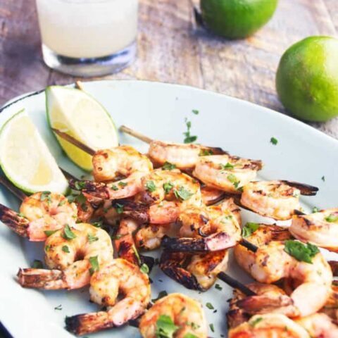 grilled tequila lime shrimp on a skewer with lime wedges and margarita and whole limes