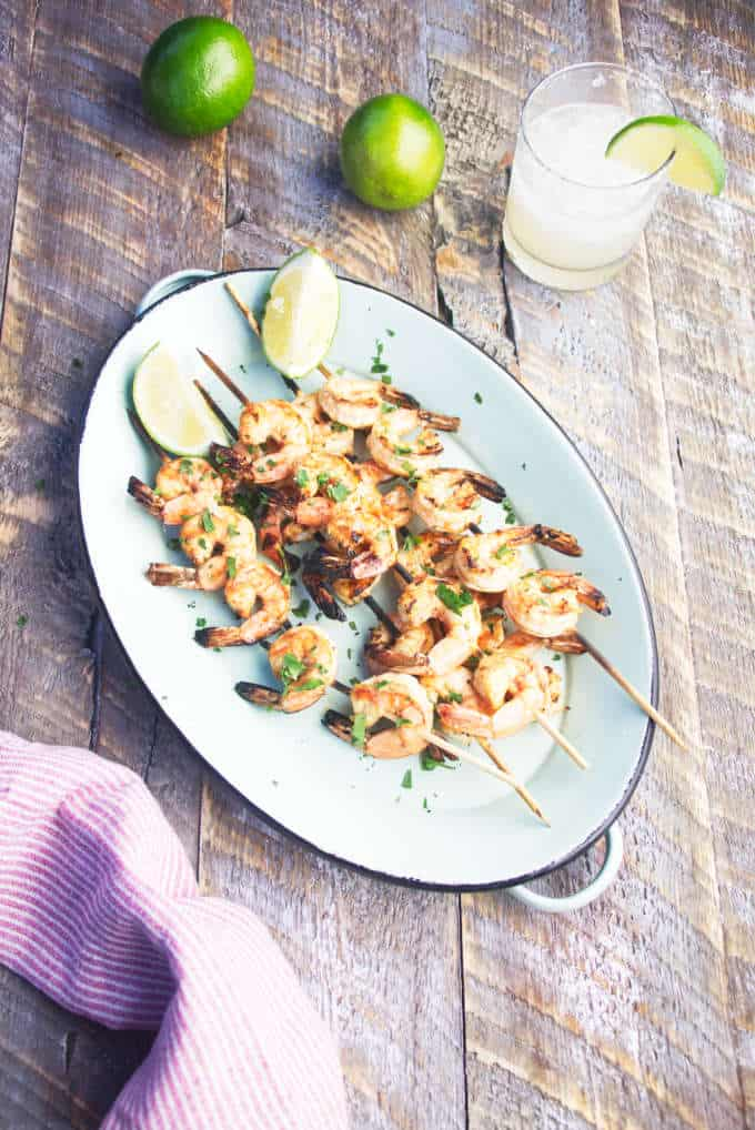 Grilled tequila lime shrimp skewers on a blue platter with limes and a margartia
