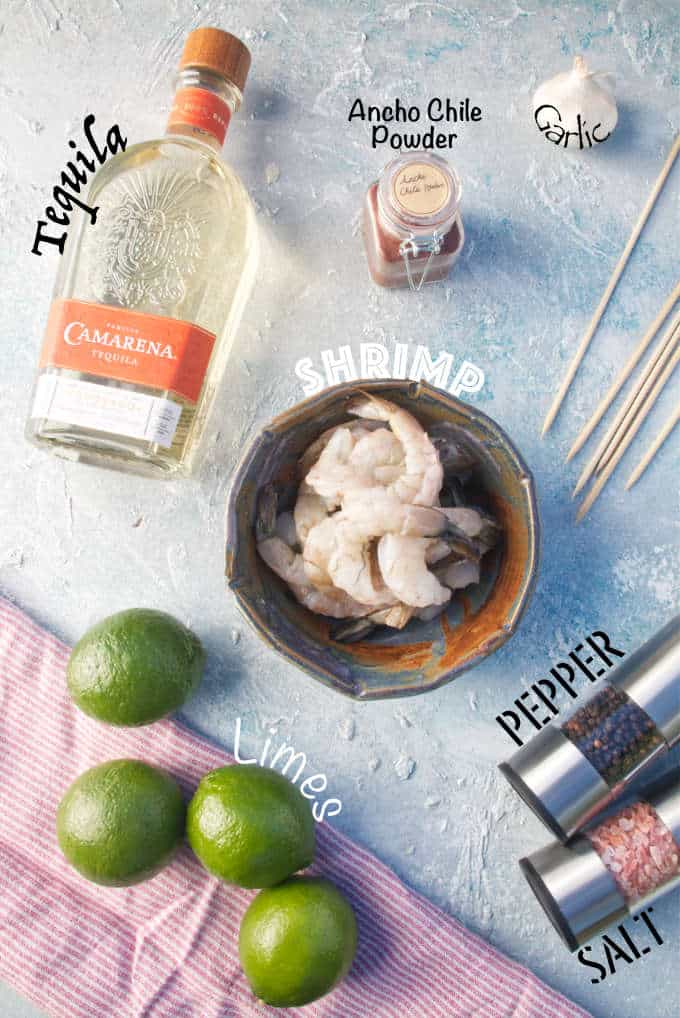 ingredients for tequila lime shrimp, garlic, ancho chile powder, pepper, salt, skewers, with red and white napkin
