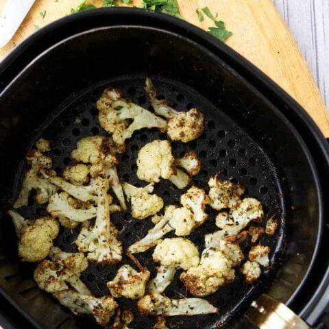 Roasted cauliflower in an air fryer basket.
