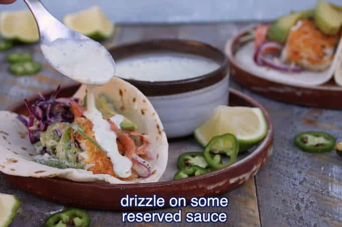 creamy sauce being drizzled over tilapia fish taco