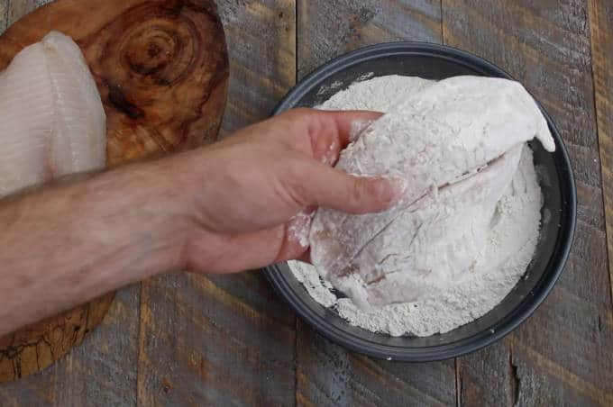 tilapia filet being coated in flour in baking pan