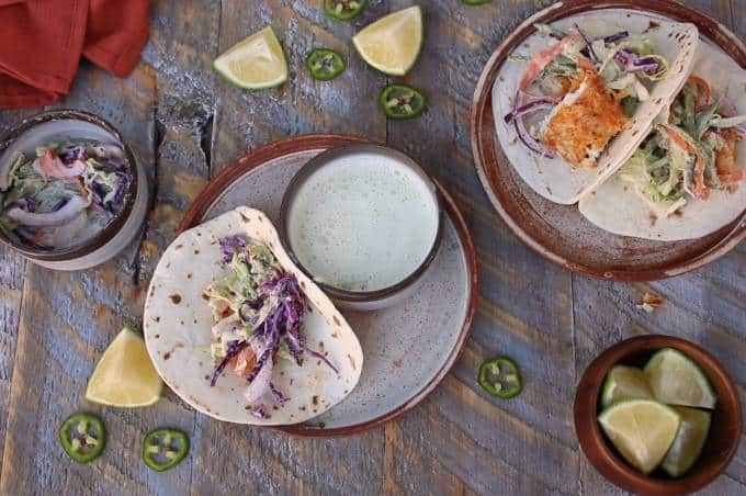 two plates on wooden table with tortillas, tilapia fish tacos being built, bed of slaw on each tortilla and chunk of tortilla in one
