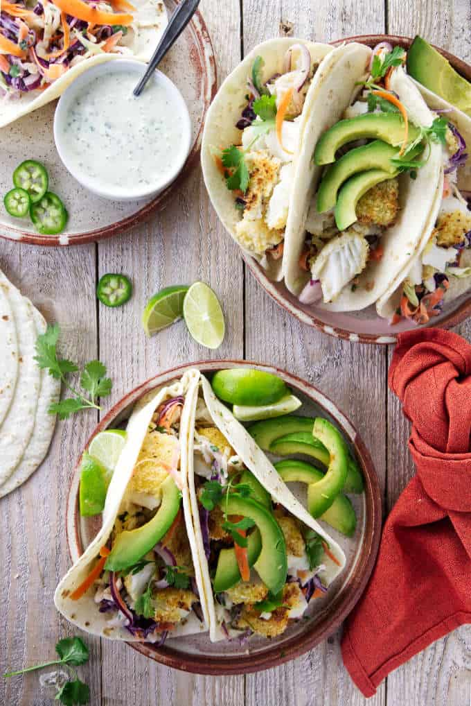 Two plates of tilapia fish tacos with avocados and lime slices.