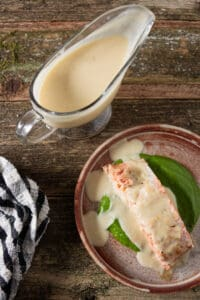 orange lemon butter sauce drizzled on top of a grilled salmon fillet with gravy boat of sauce