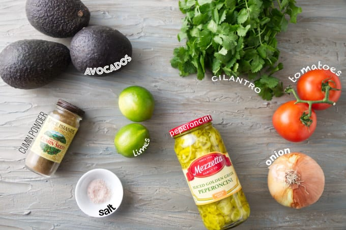 Ingredients used to make guacamole with tomatoes and pepperoncini.