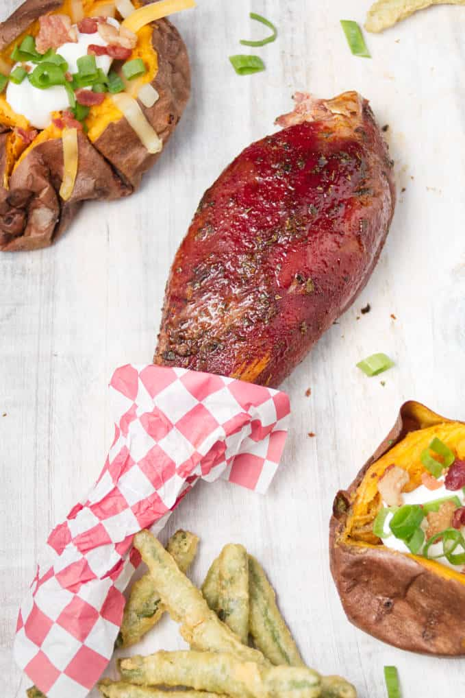 Smoked wild turkey leg laying on white cutting board with loaded baked sweet potatoes and some fried green beans