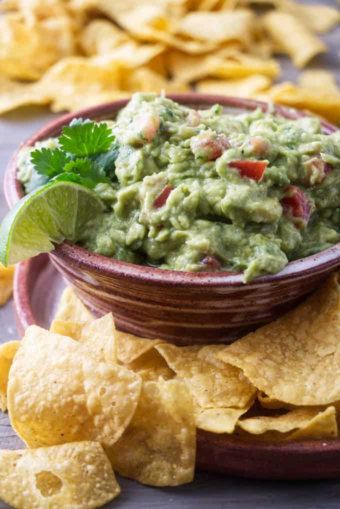 a serving dish of guacamole surrounded by corn chips.