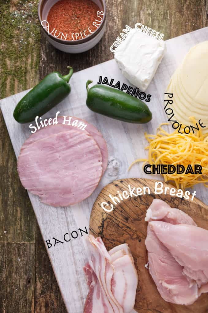 Ingredients for smoked jalapeño popper chicken: cajun spice rub, cream cheese, jalapeños, sliced ham, provolone cheese, cheddar cheese, bacon, and chicken breast.