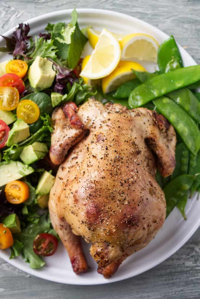 A smoked Cornish game hen on a plate with peas and salad.